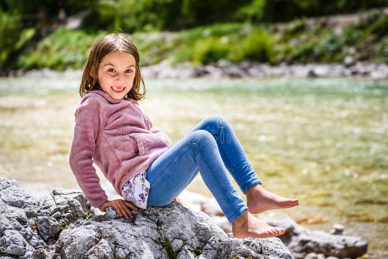 Little girl sitting on river rock after nature hiking royalty free stock photo