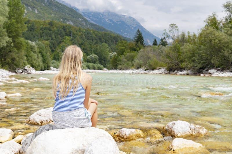 Little girl sitting on river rock, river Soca, Bovec, Slovenia. Alps, traveler, destination, scenic, tourist, mountain, europe, julian, people, kid, vacation stock image