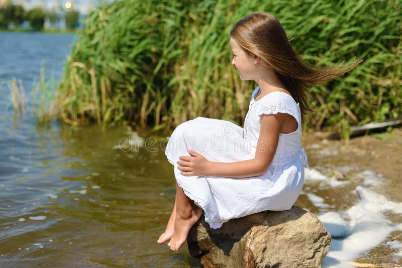 Little girl is sitting on a rock in white dress on sunny day stock photography