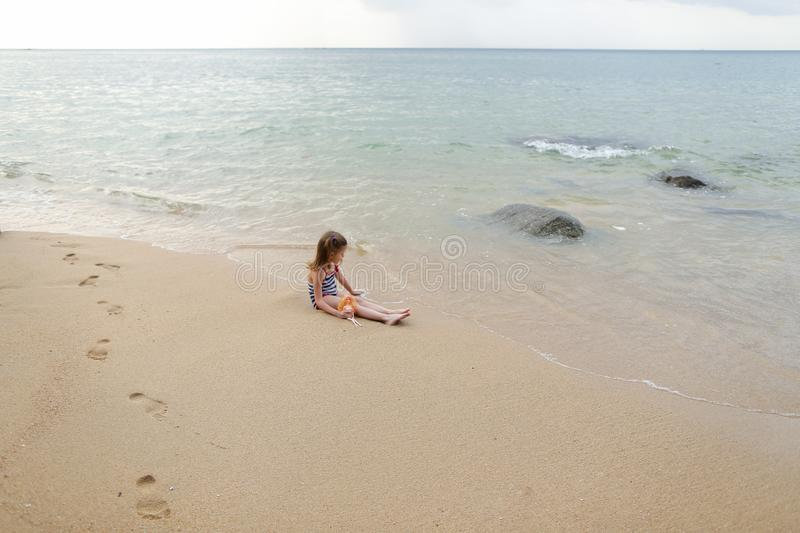 Little girl sitting on sand near sea and playing with doll. royalty free stock photos