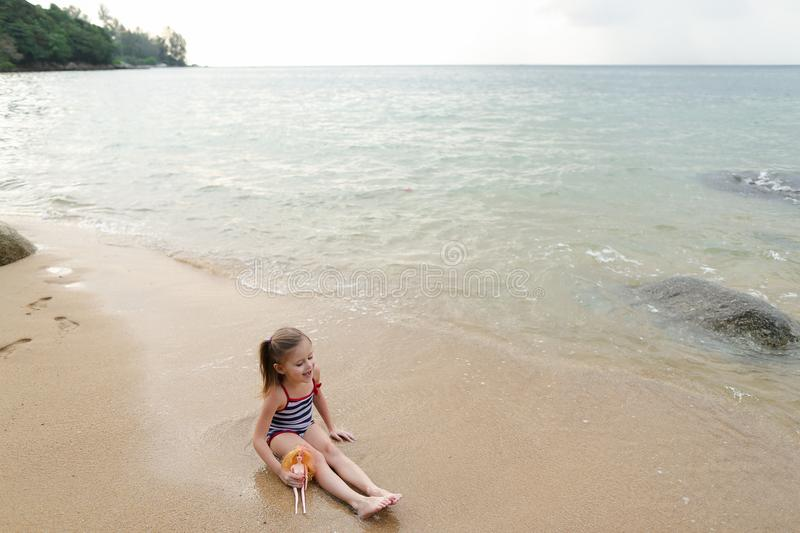 Little girl sitting on sand near sea and playing with doll. royalty free stock images