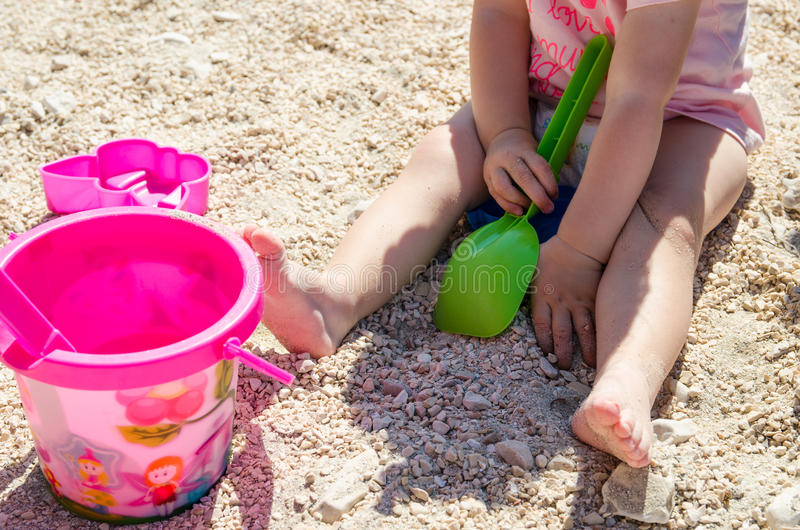 Little girl sitting on the sand and playing with plastic toys. royalty free stock image