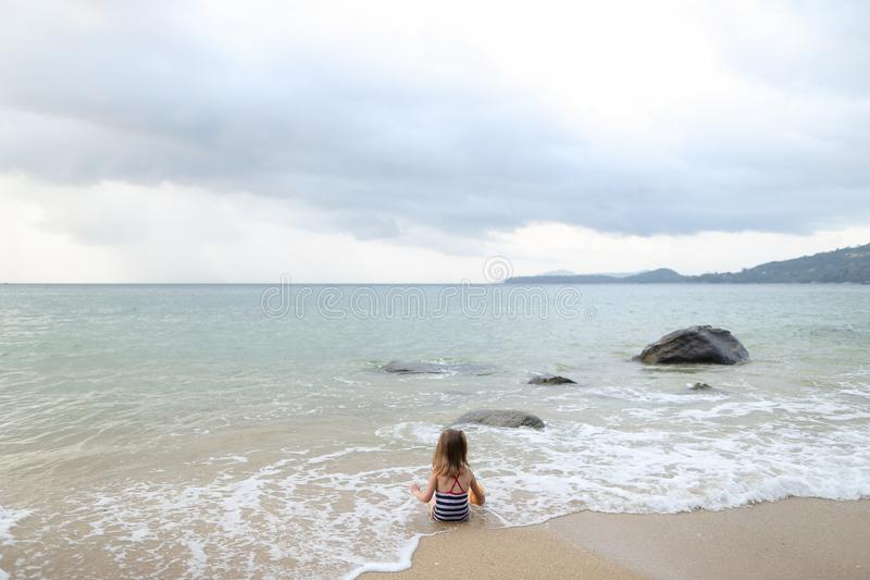 Little girl sitting on sand in sea waves in morning. royalty free stock photo