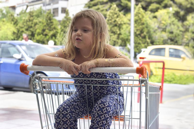 Little girl sitting in shopping cart royalty free stock photo