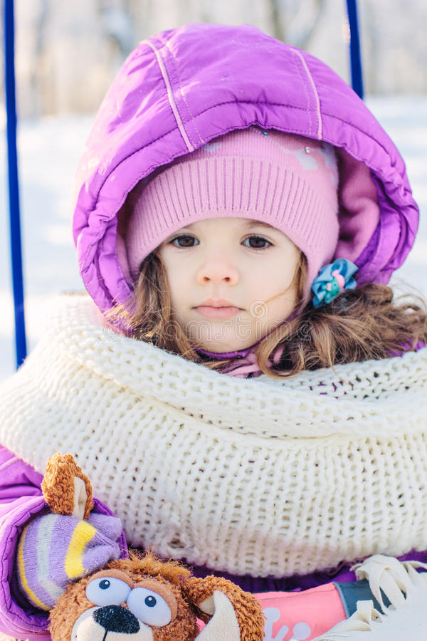 Little girl sitting in the sled on winter park stock photography