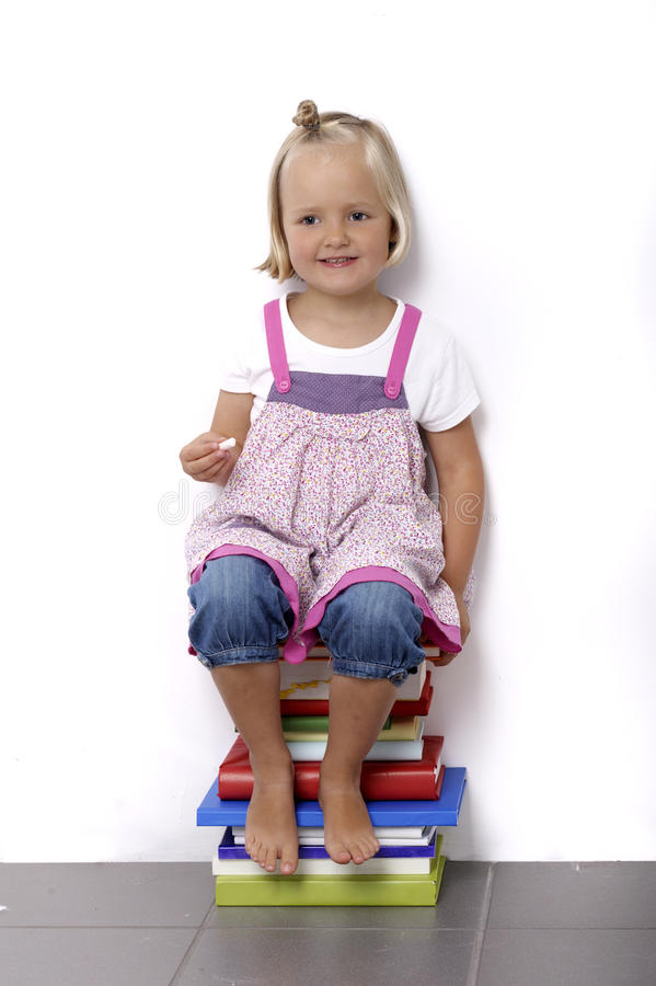 Download Little Girl Sitting On A Stack Of Books Stock Photo - Image: 20531840