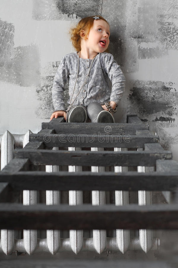 Little girl sitting on stairs and making faces stock photography