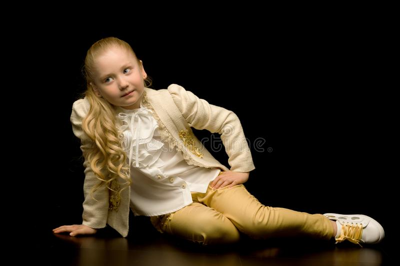 A little girl is sitting in the studio on the floor on a black b stock image