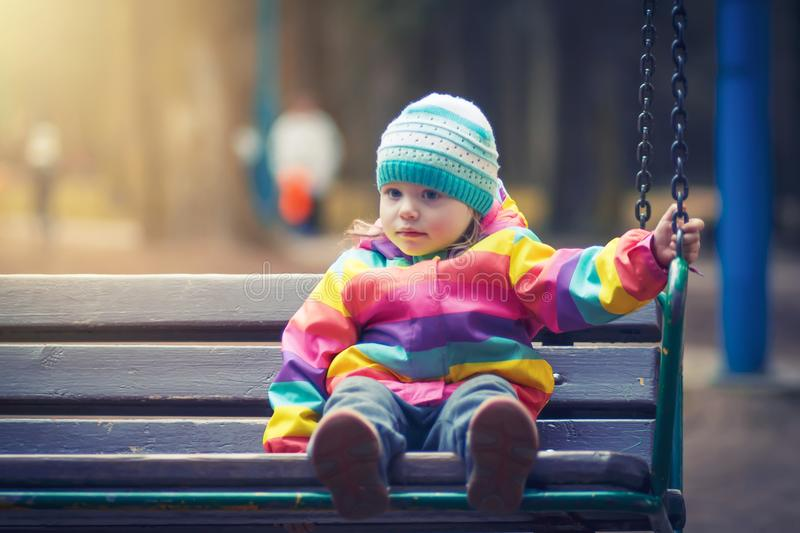 Little girl is sitting on swing in evening park. child is riding wooden swing on dark evening under light from lanterns. royalty free stock photo