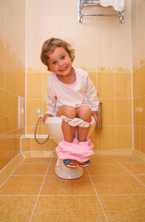 Little girl is sitting on toilet stock photo