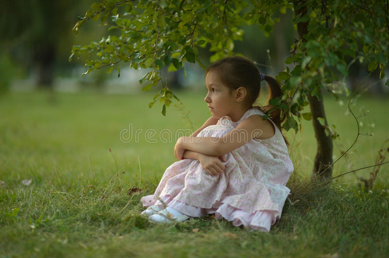 Little girl sitting under tree royalty free stock photography