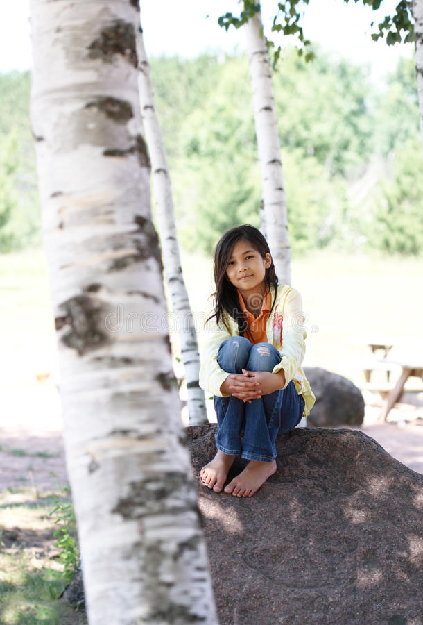 Download Little Girl Sitting Under Trees Stock Photo - Image: 10260988