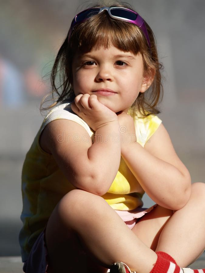 Little girl sitting watching others, summer weather, neutral background. 2 royalty free stock image