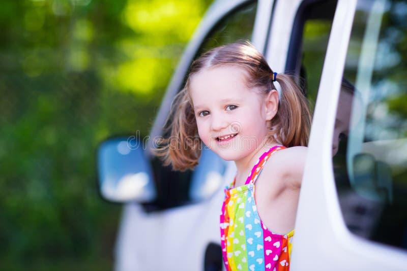 Little girl sitting in white car stock photo
