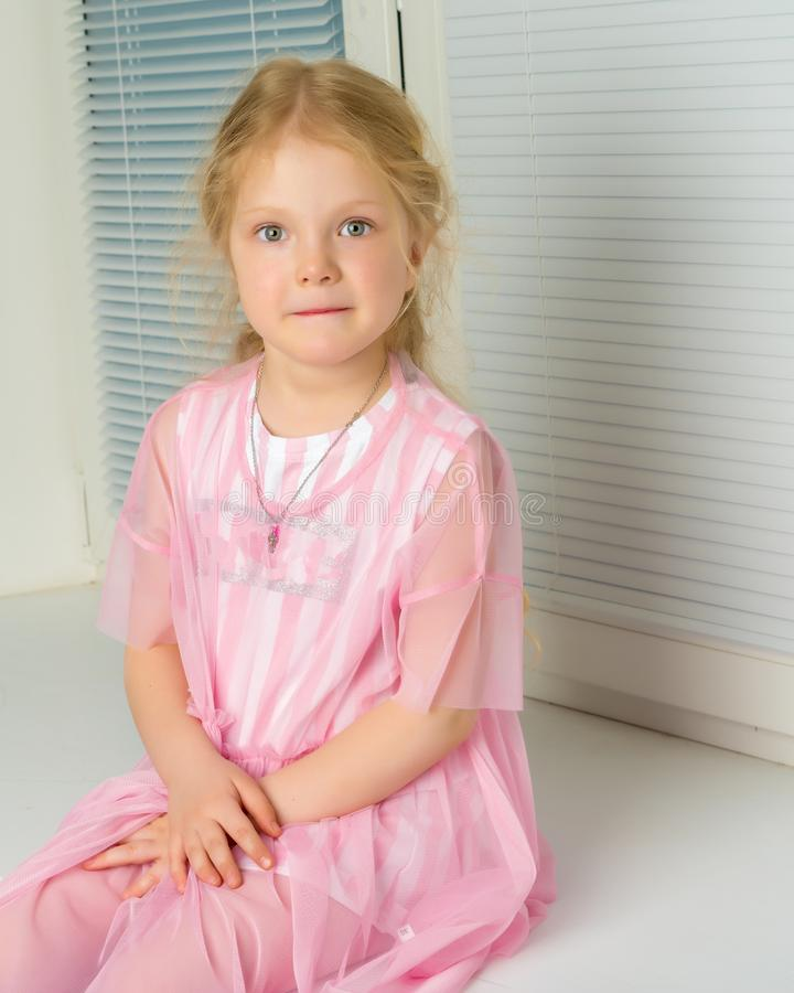A little girl is sitting by the window with jalousie stock photos