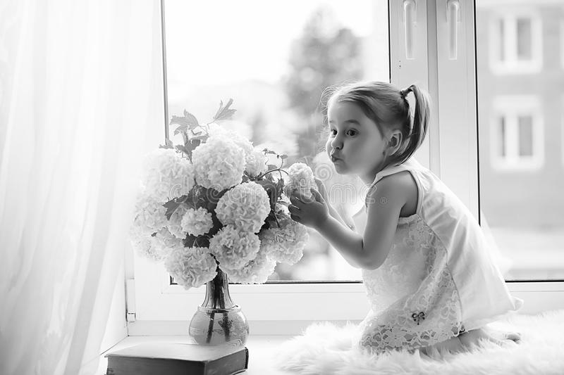 A little girl is sitting on the windowsill. A bouquet of flowers royalty free stock photo