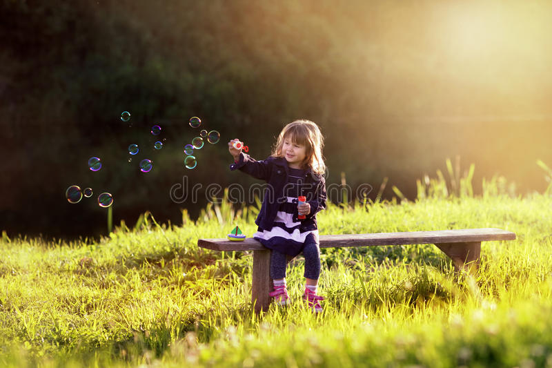 Little girl sitting on a wooden bench blows bubbles stock photography