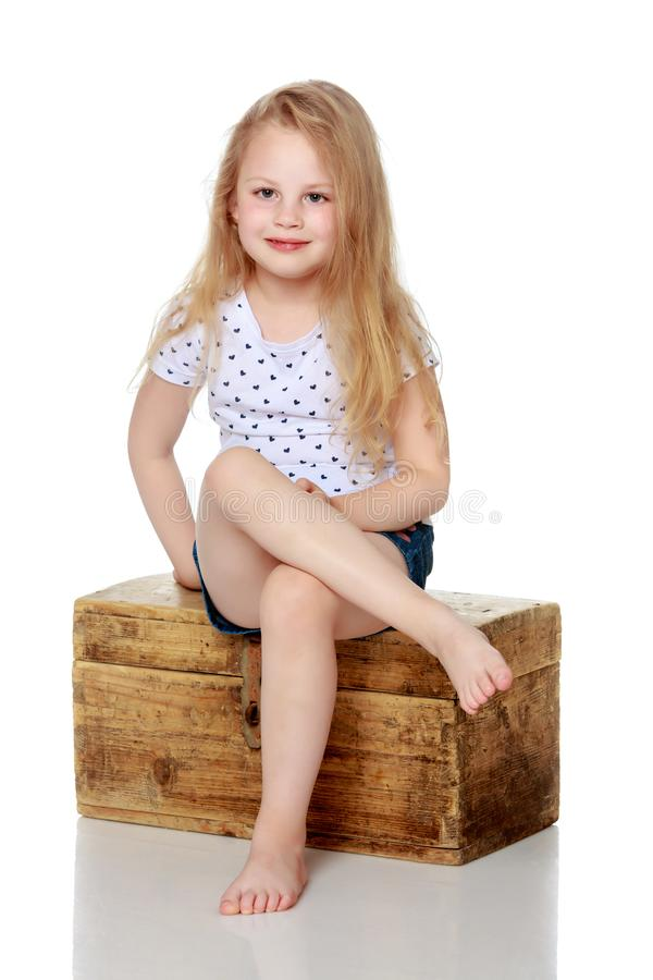 A little girl is sitting on a wooden box. stock photo