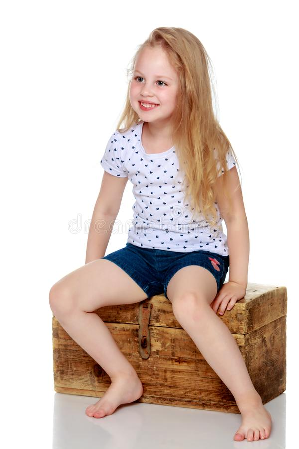 A little girl is sitting on a wooden box. royalty free stock photo