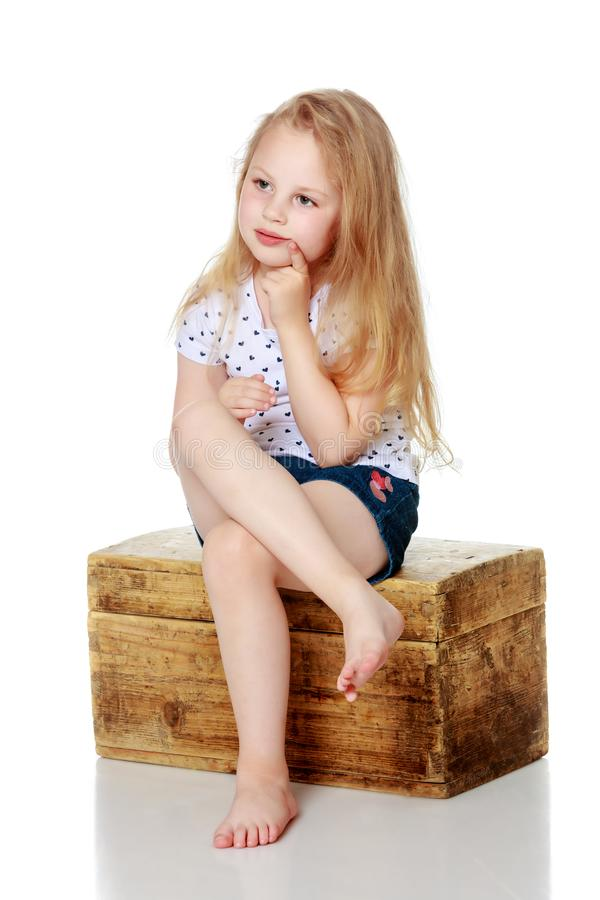 A little girl is sitting on a wooden box. stock image