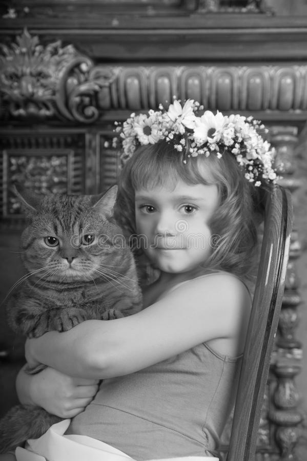 Little girl sitting with a wreath of flowers on her head with a big fat cat stock photo