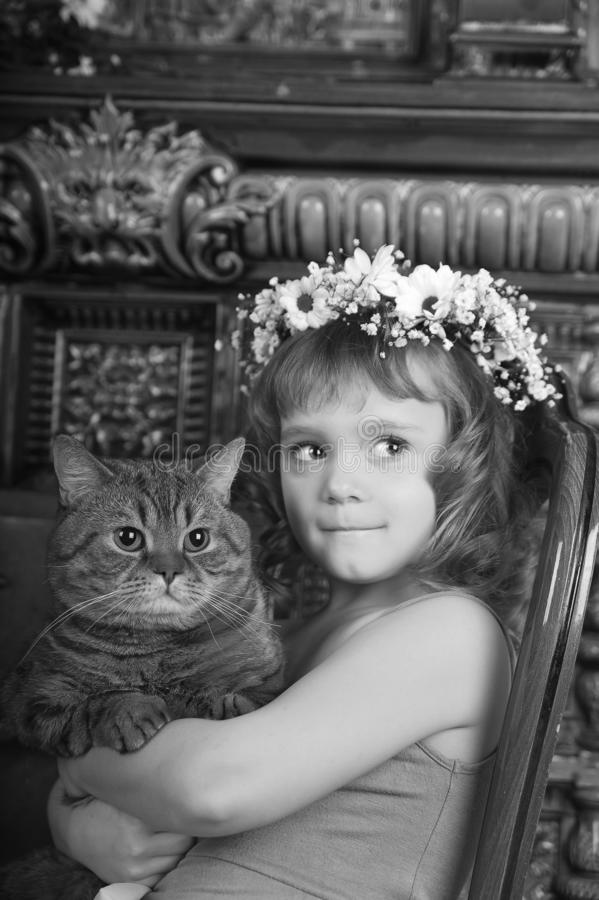 Little girl sitting with a wreath of flowers on her head with a big fat cat stock photos