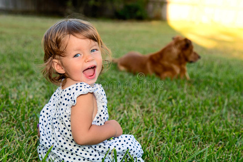 Little girl sitting in yard smiling royalty free stock images