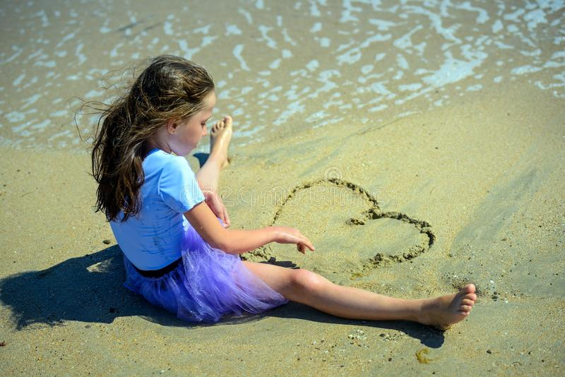 A little girl sitting on the yellow sand on the beach in a purple dress and draws a heart with her hands on the sand. stock photos