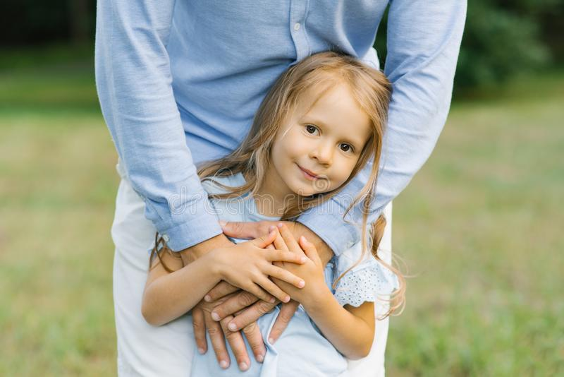 A little girl of six or five in a blue dress holds her father`s hands and smiles sweetly .  the girl and her father stock photos