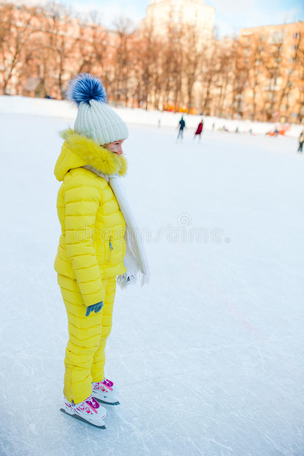Little girl skating on the ice rink outdoors enjoy winter day. Adorable little girl skating on the ice-rink royalty free stock photos