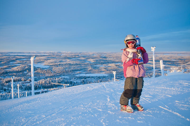 Little girl-skier on the hill watching the sunrise stock photo