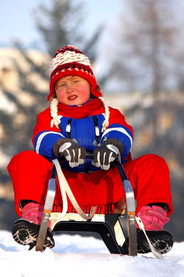 Little girl sledding royalty free stock photo