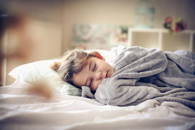 Morning in bed. Little girl sleeping in bed. Space for copy stock photo