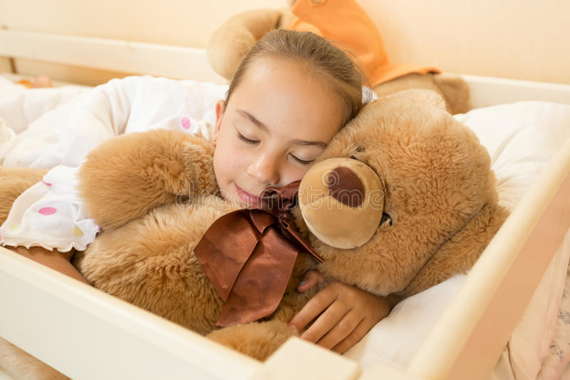 Little girl sleeping on big teddy bear at bed. Portrait of little girl sleeping on big teddy bear at bed royalty free stock image