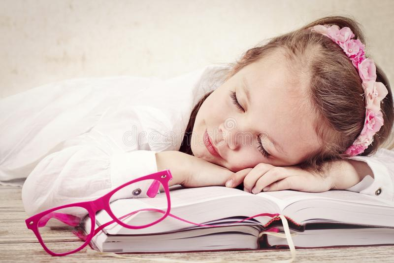 Little girl sleeping on the books stock images