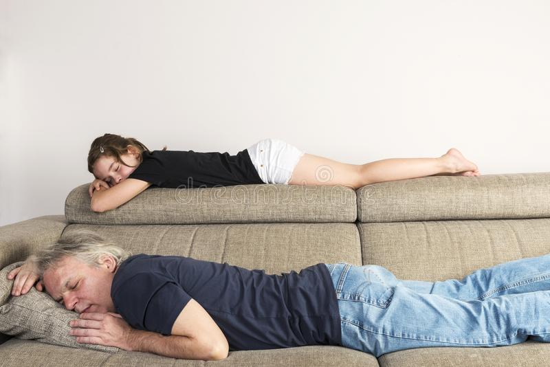 Little girl sleeping with her dad on the couch royalty free stock images