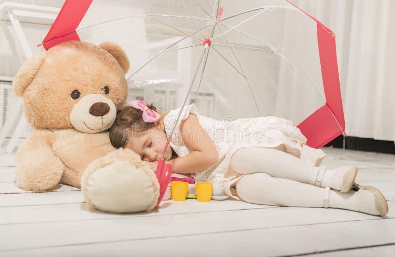 Little girl sleepingin under umbrela in her teddy bear arms. Beautiful little girl sleeping under umbrella in her teddy bear arms after tea party stock photos