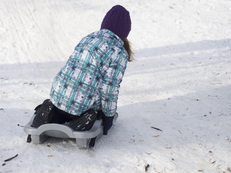 Little girl on a sleigh stock photos