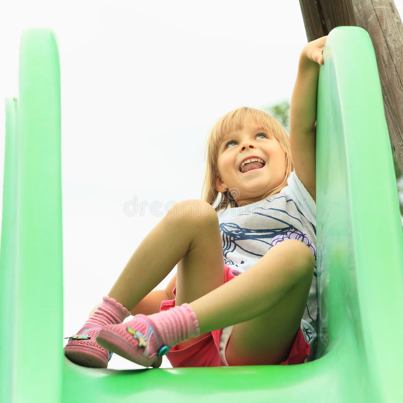 Little girl on a slide stock photography