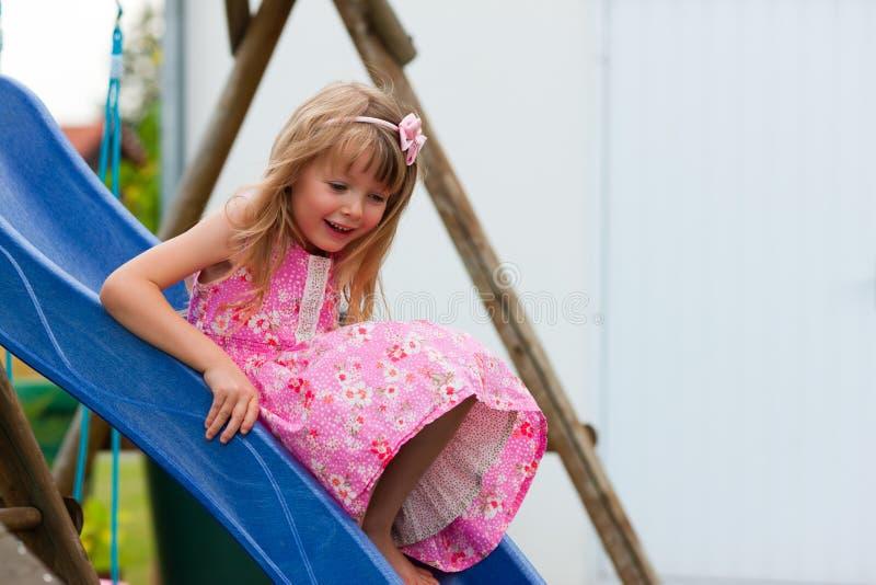 Little girl on slide in summer