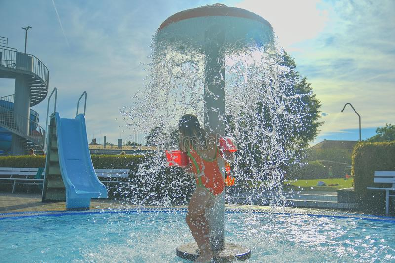 Little girl in the small swimming pool. Cute girl take shower in water park. Summer and happy chilhood concept stock images