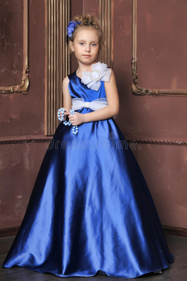 Little girl in a smart blue dress. Young princess in a beautiful blue ball gown stock images