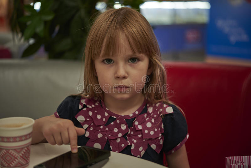 Little girl with a smartphone stock photography