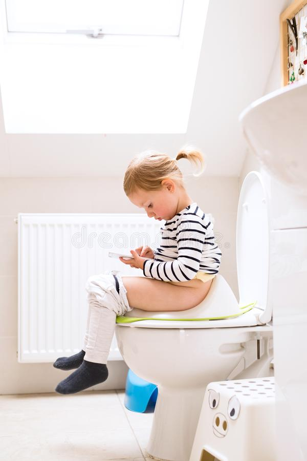 Little girl with smartphone sitting on the toilet. royalty free stock image