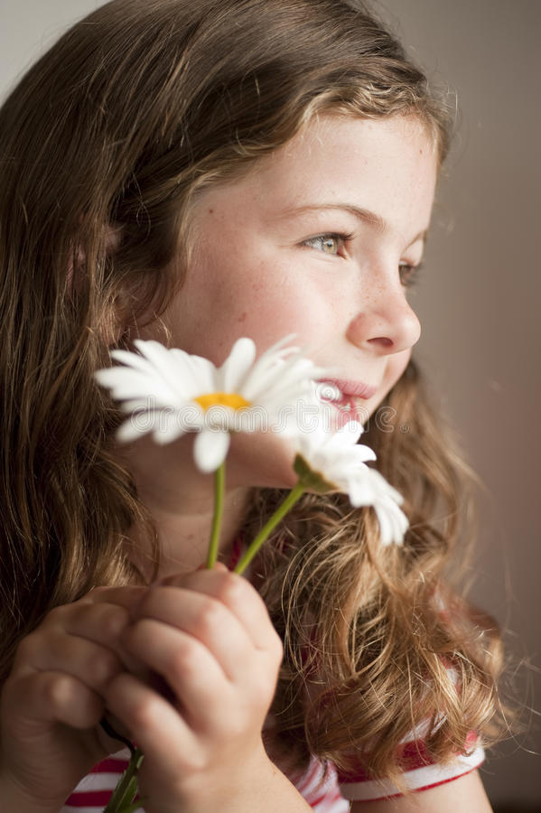 Little girl smelling daisies royalty free stock photos