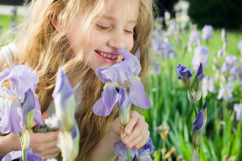 Little girl smelling flower royalty free stock images