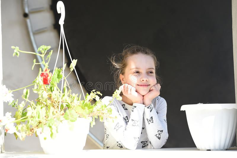 Little girl smile with flowers on sunny day. Happy child and childhood. Beauty kid with plant pots in summer or spring. Freshness royalty free stock images