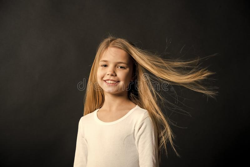 Little girl smile with long blond hair on black background. Happy child with fashion hairstyle. Beauty kid smiling with stock images