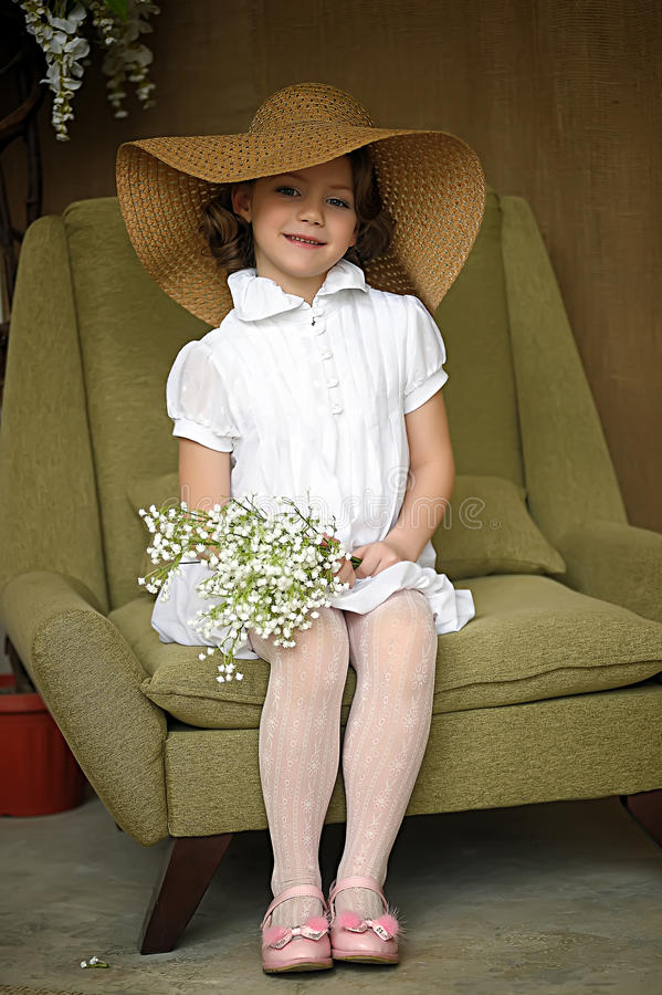 little girl with a smile in a wide-brimmed straw hat in a bouquet of white lilies of the valley in the hands royalty free stock photo