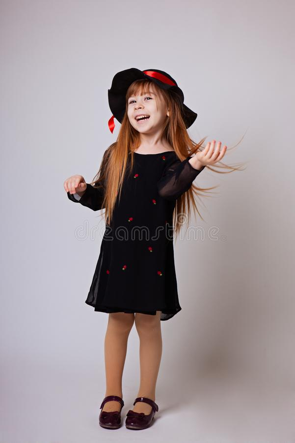 Little girl smiling in a black dress and black hat with a red ri stock images
